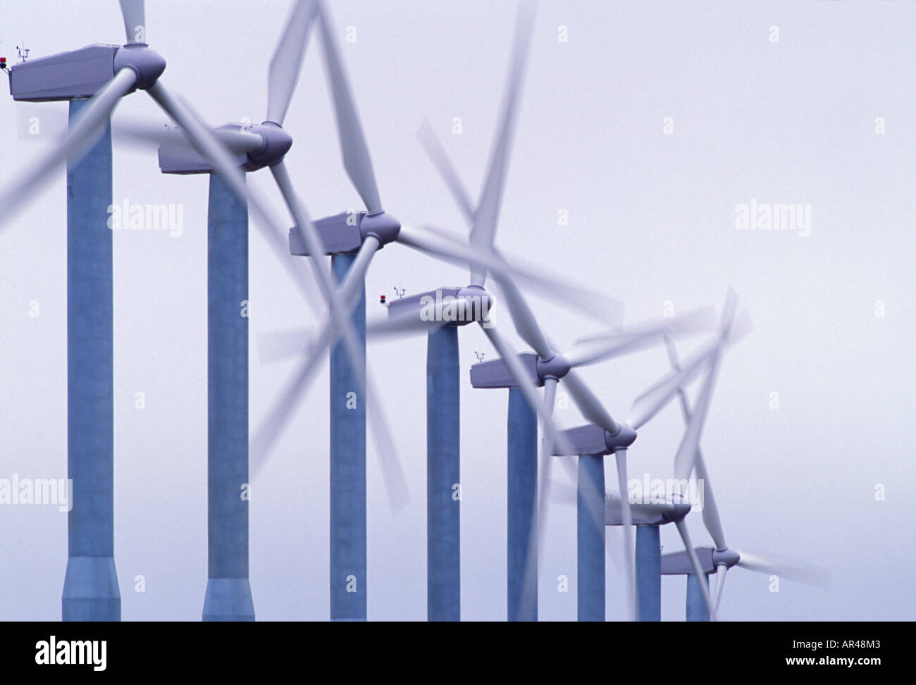 The propeller blades of wind turbines spin in the wind against a gray sky - Stock Image