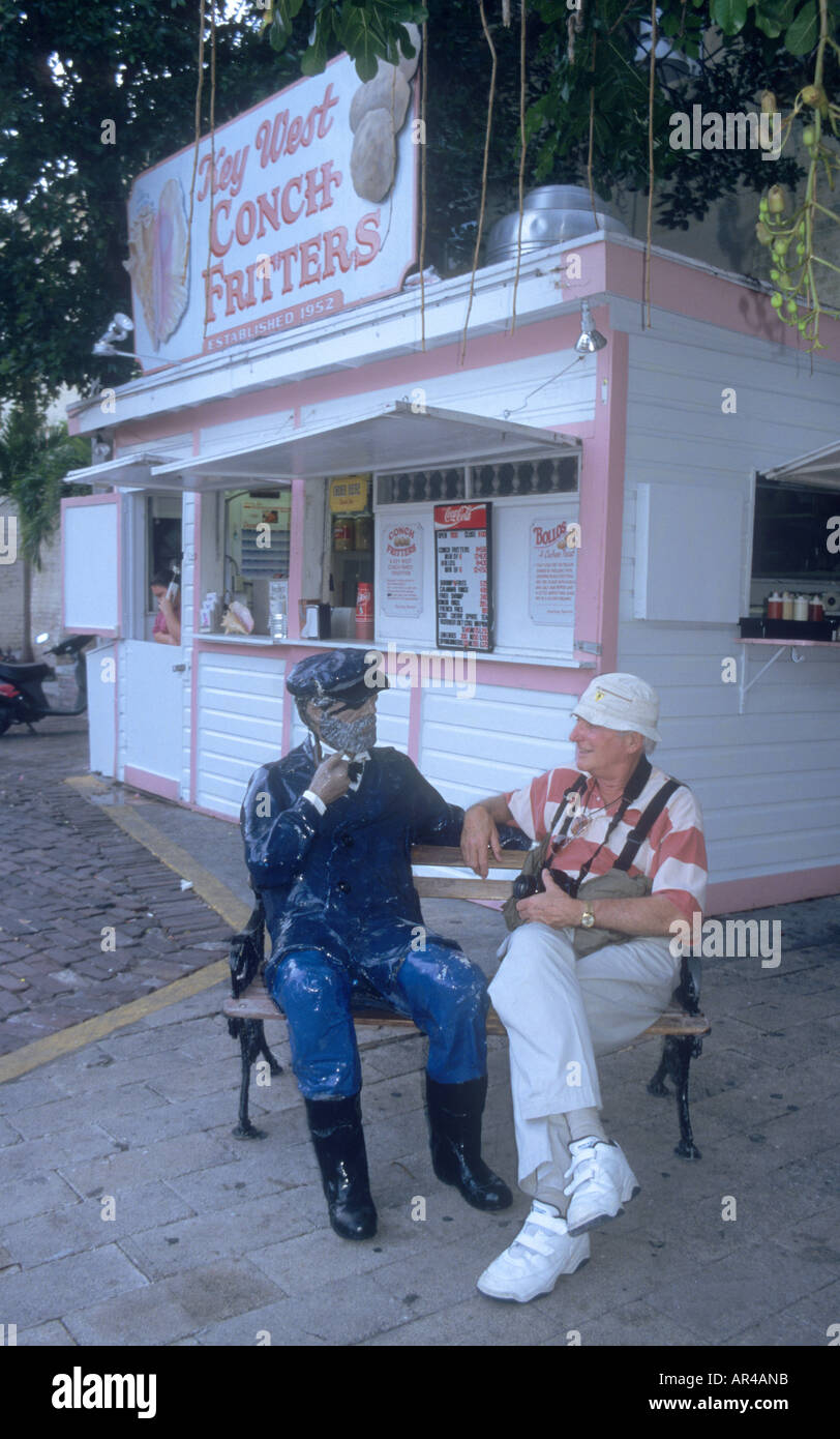 tourist enjoys the local delicacy ,Conch Fritters,on Key West Florida - Stock Image
