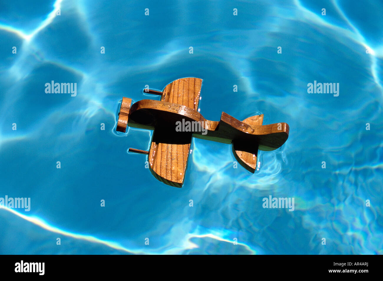 A wooden aircraft on a swimming pool - Stock Image