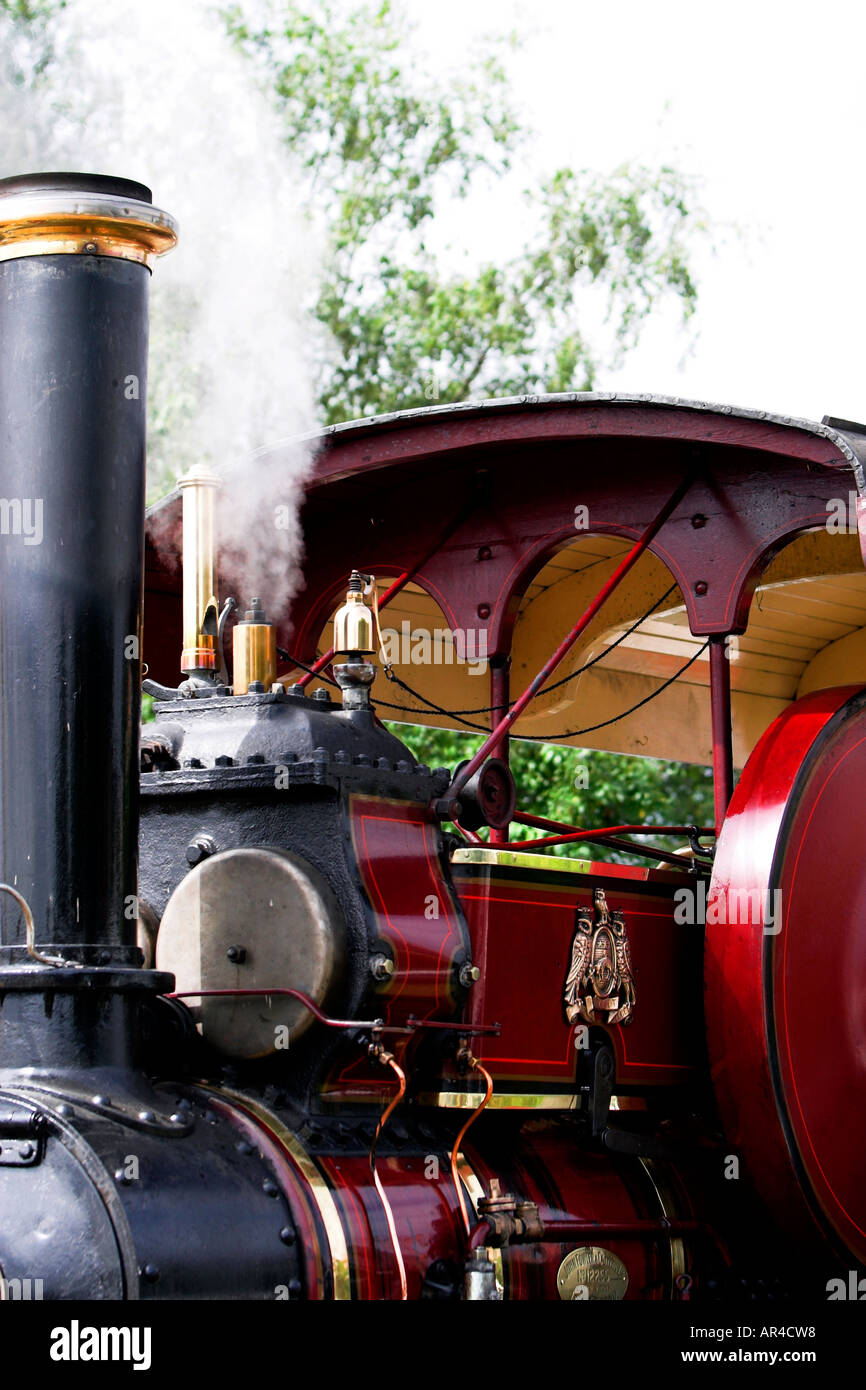 A crop of a steam traction engine showing its funnel and whistle in action the flywheel and the cabin above the boiler is in red - Stock Image