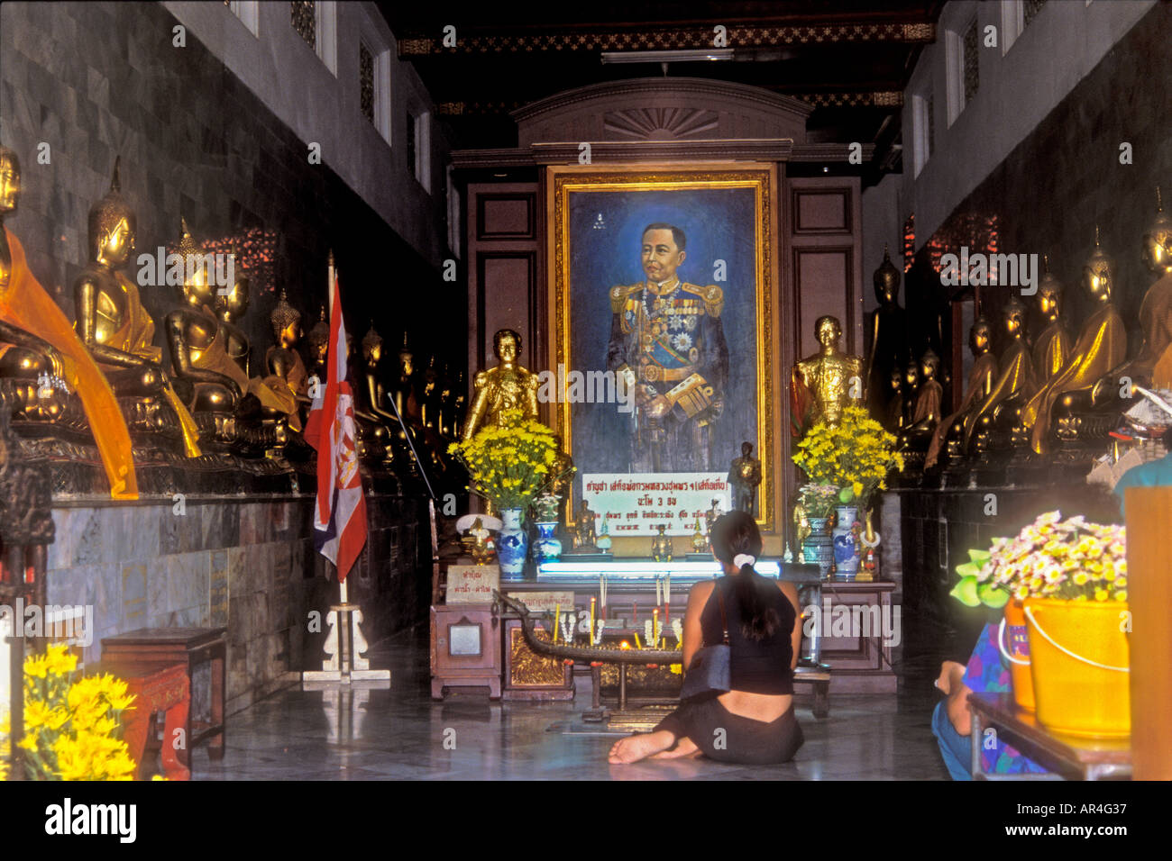 Shrine interior with female worshipper at temple of Wat Po,  Bangkok, Thailand - Stock Image