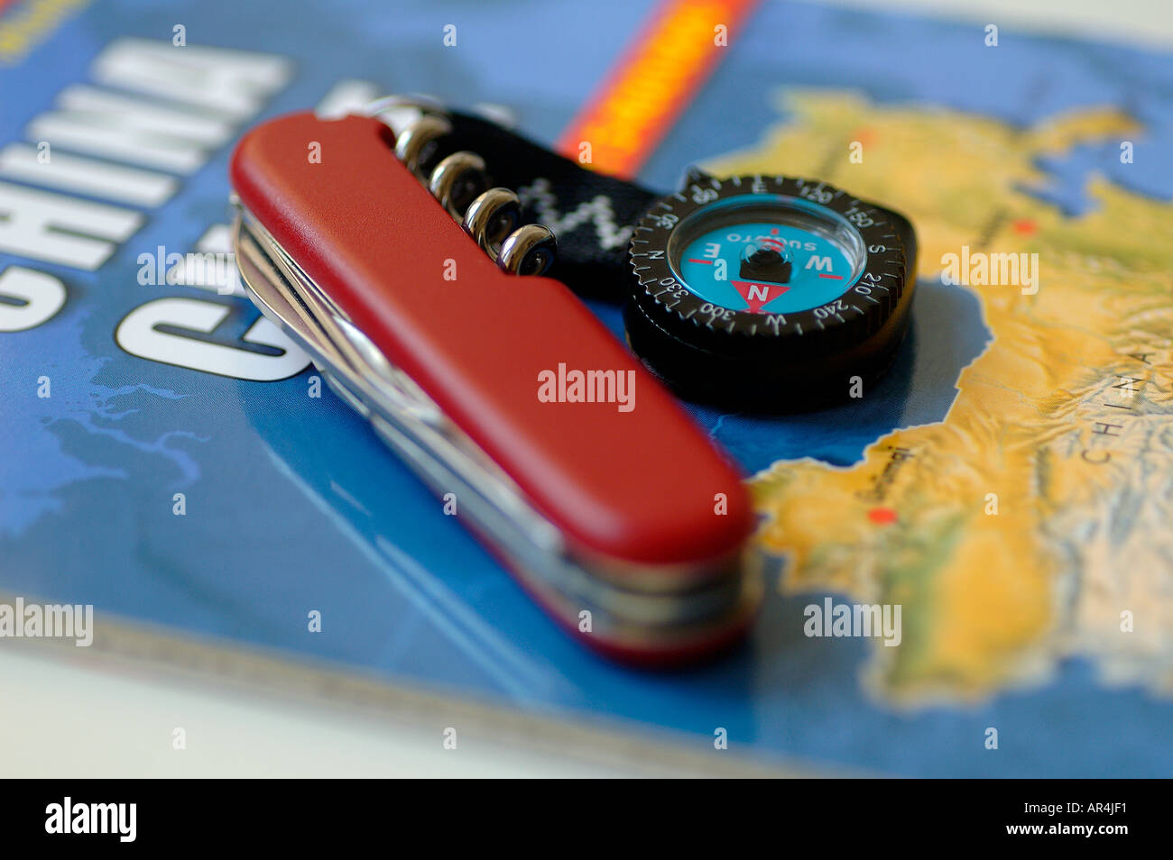 Small compass with Swiss army knife on china map - Stock Image
