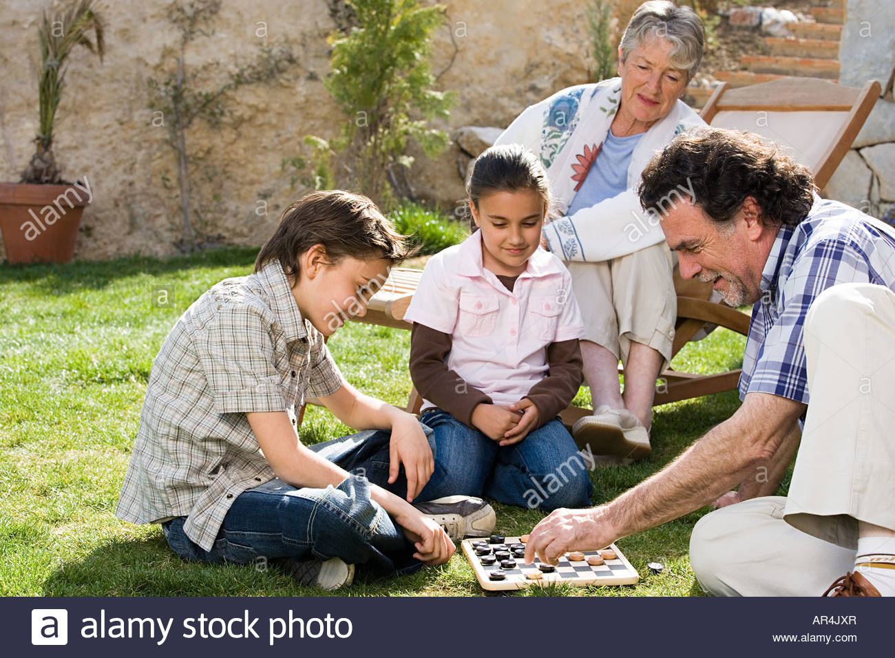 Grandparents and grandchildren playing draughts - Stock Image