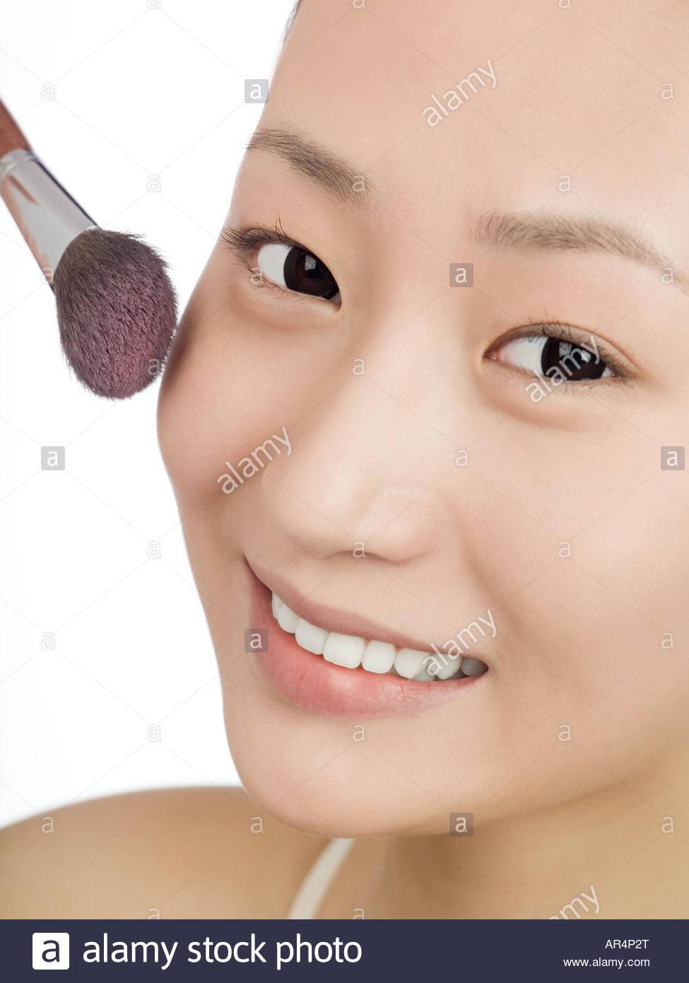 Chinese woman applying blusher - Stock Image
