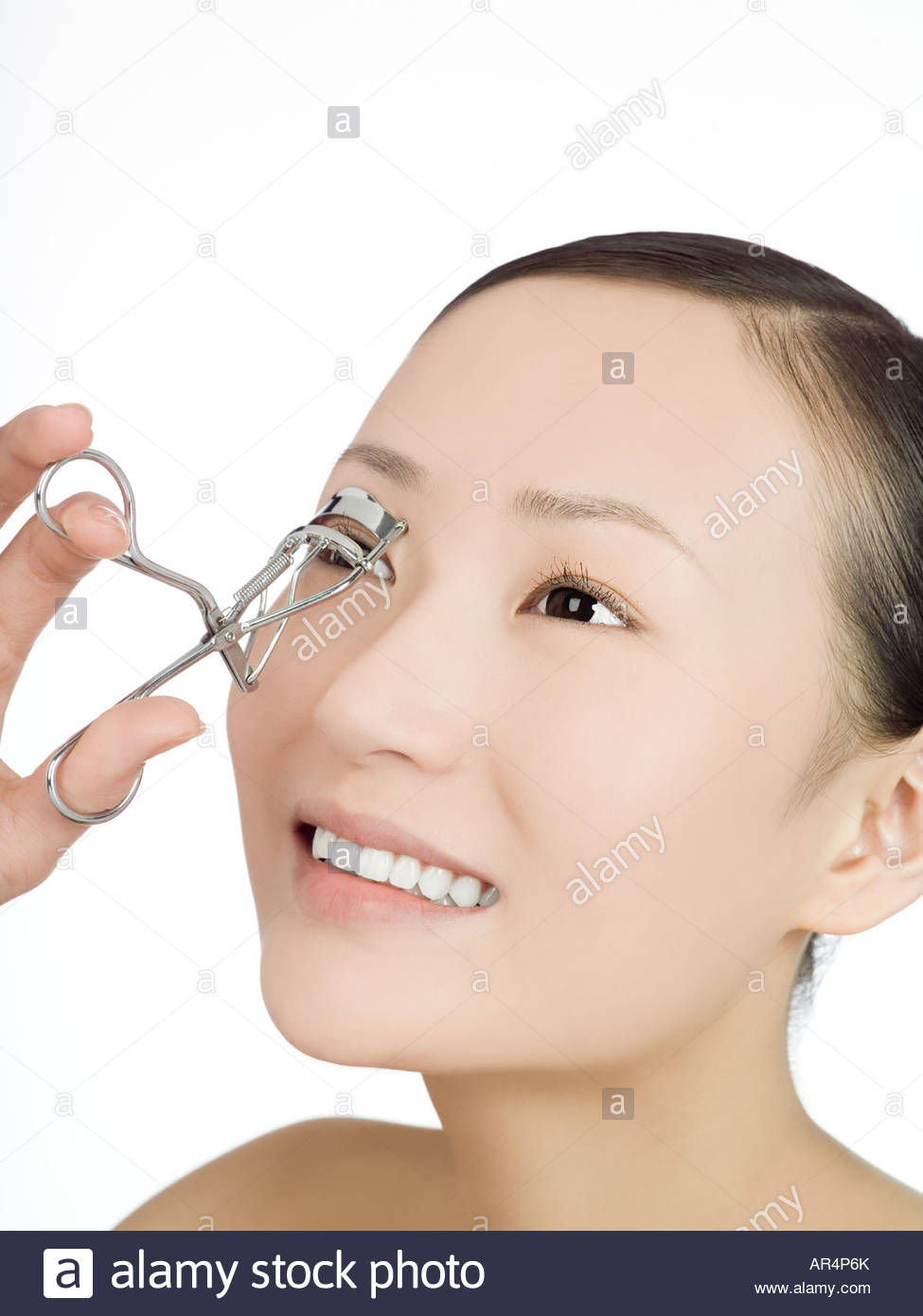 Chinese woman curling her eyelashes - Stock Image
