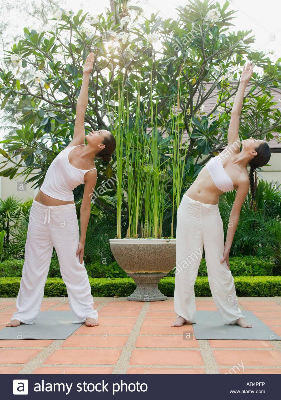 Two women practising yoga - Stock Image