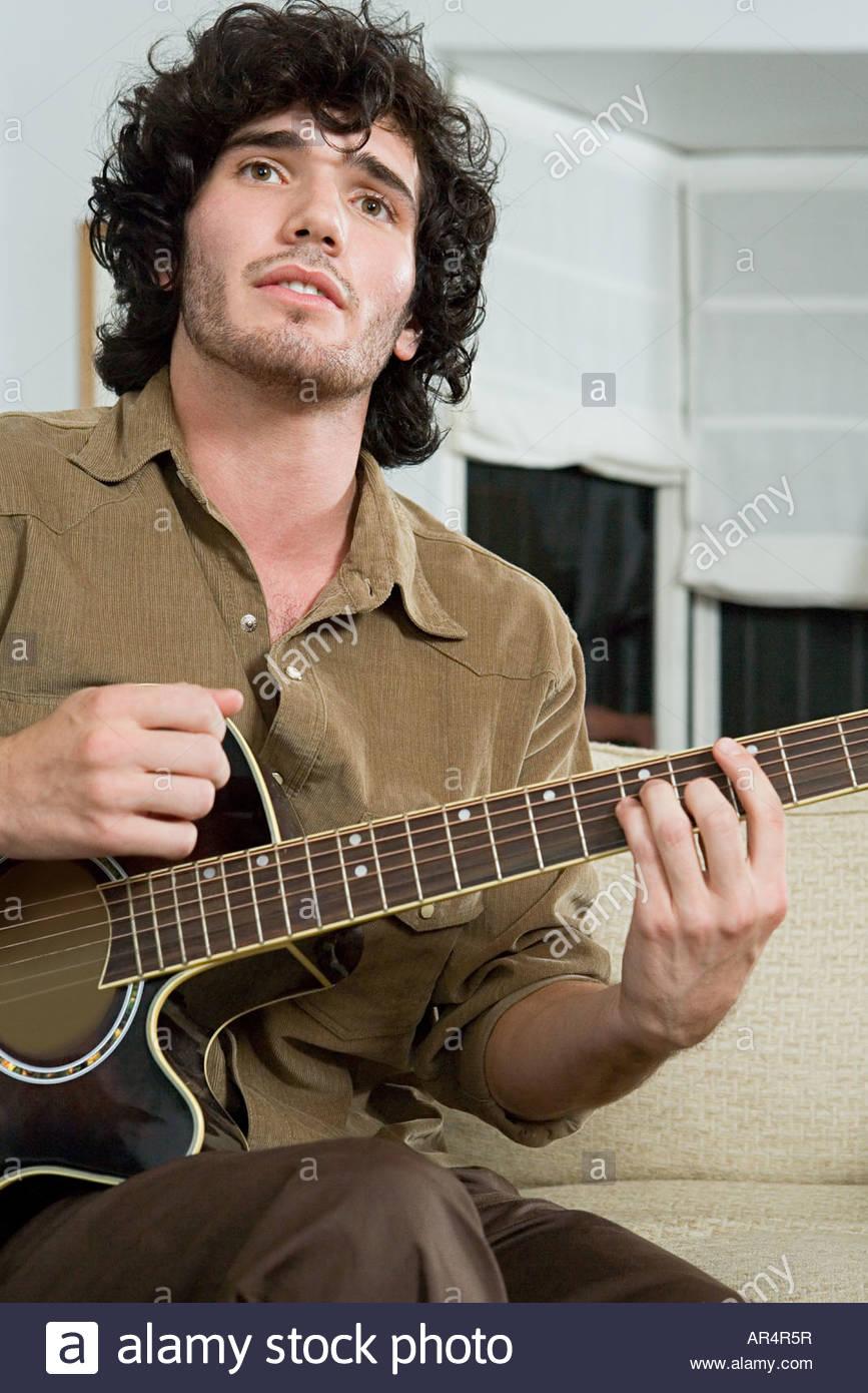 Young man playing a guitar - Stock Image