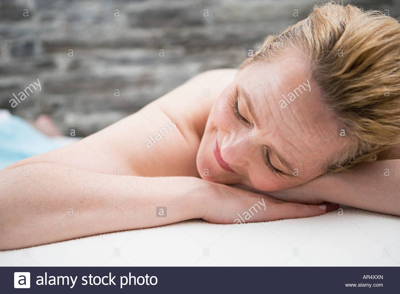 Woman sleeping on a treatment couch - Stock Image