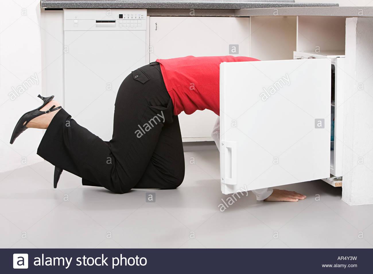 Businesswoman looking in fridge - Stock Image