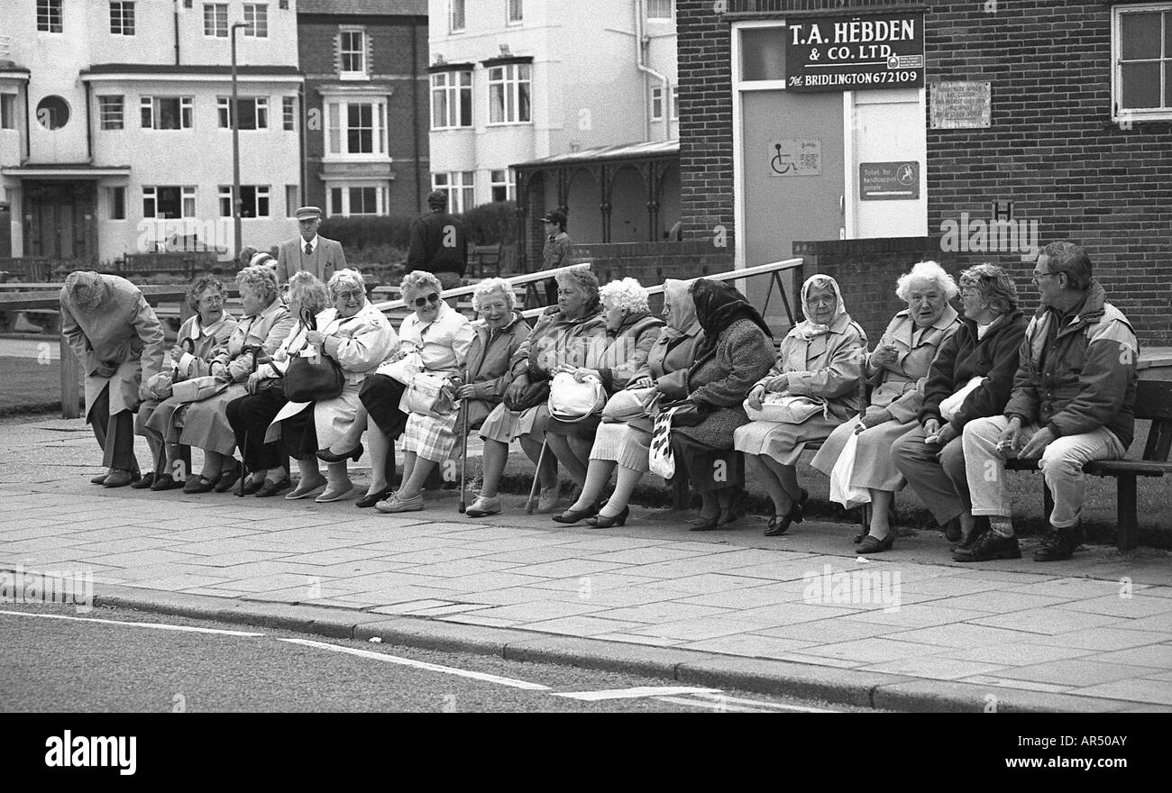 Large number of old people who are mostly women sitting on a long bench at a seaside resort in England. - Stock Image