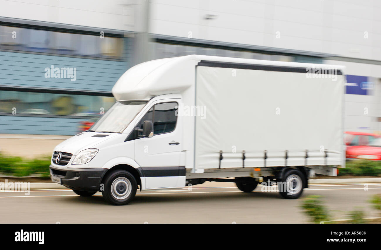 a05c1e10650d0e Mercedes benz sprinter luton curtain sided truck speeding along a road in  England.