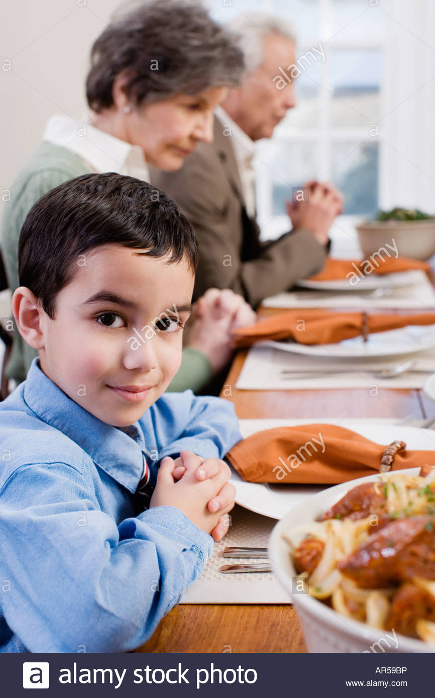 Boy and family saying grace - Stock Image