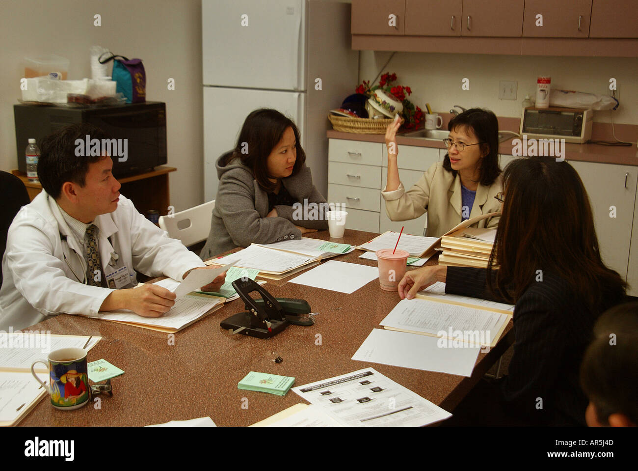 Woman speaks at doctor/staff meeting: Vietnamese-American community clinic, Garden Grove, California, USA. MODEL RELEASE - Stock Image