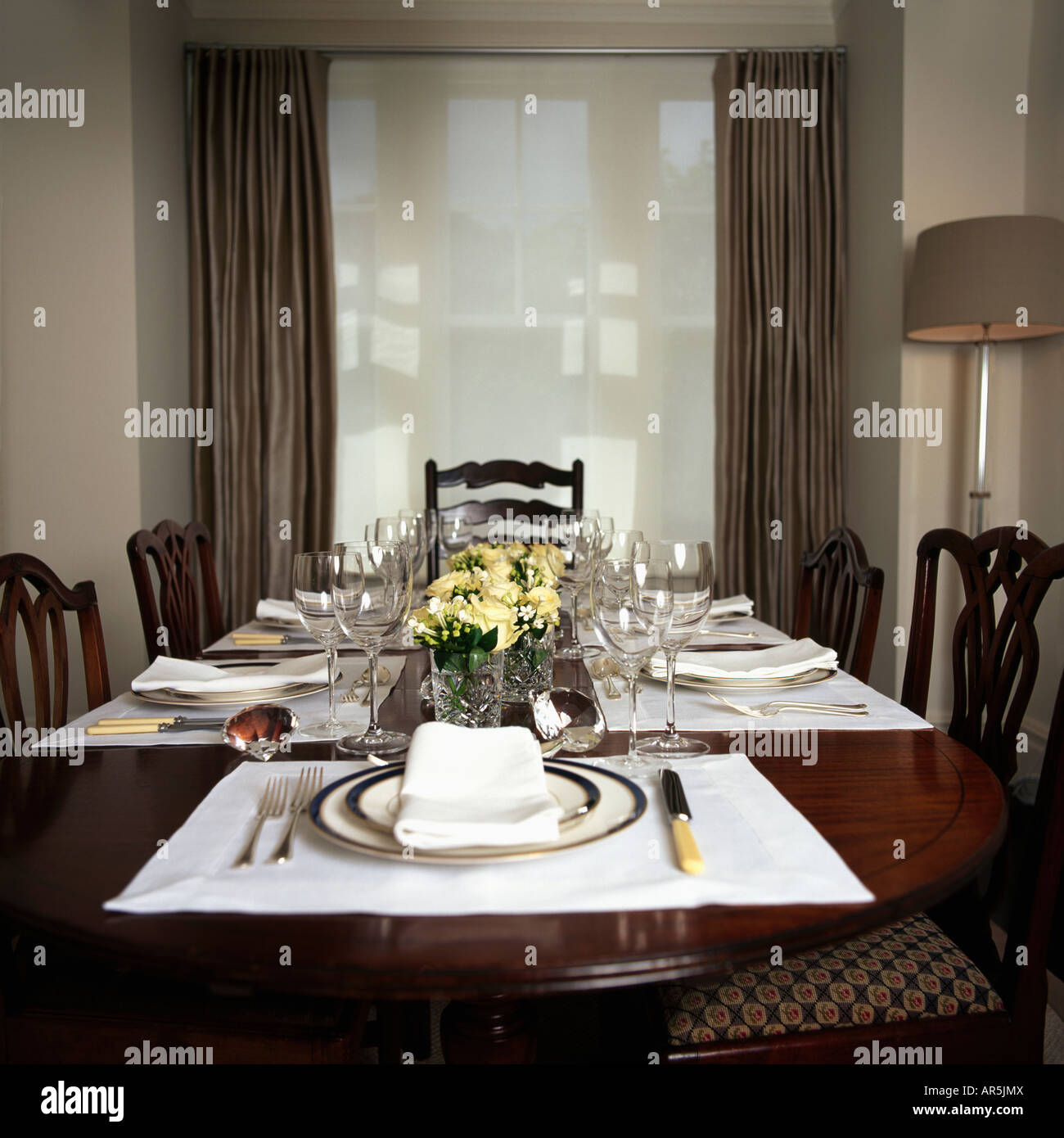 White Placemats And Plates In Modern Grey Dining Room With Blind Curtains