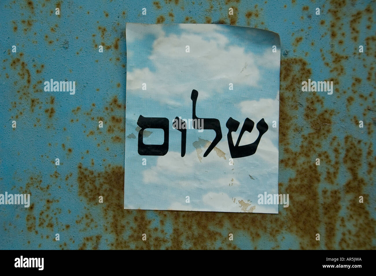 Paper leaflet with the word 'Peace' in Hebrew attached to a rusted metal door in Israel - Stock Image