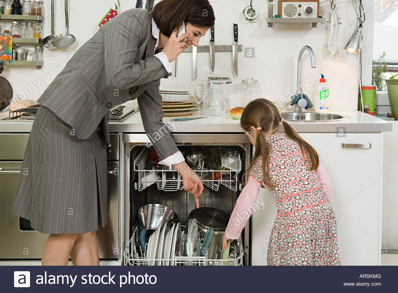 Daughter helping mother with filling dishwasher - Stock Image