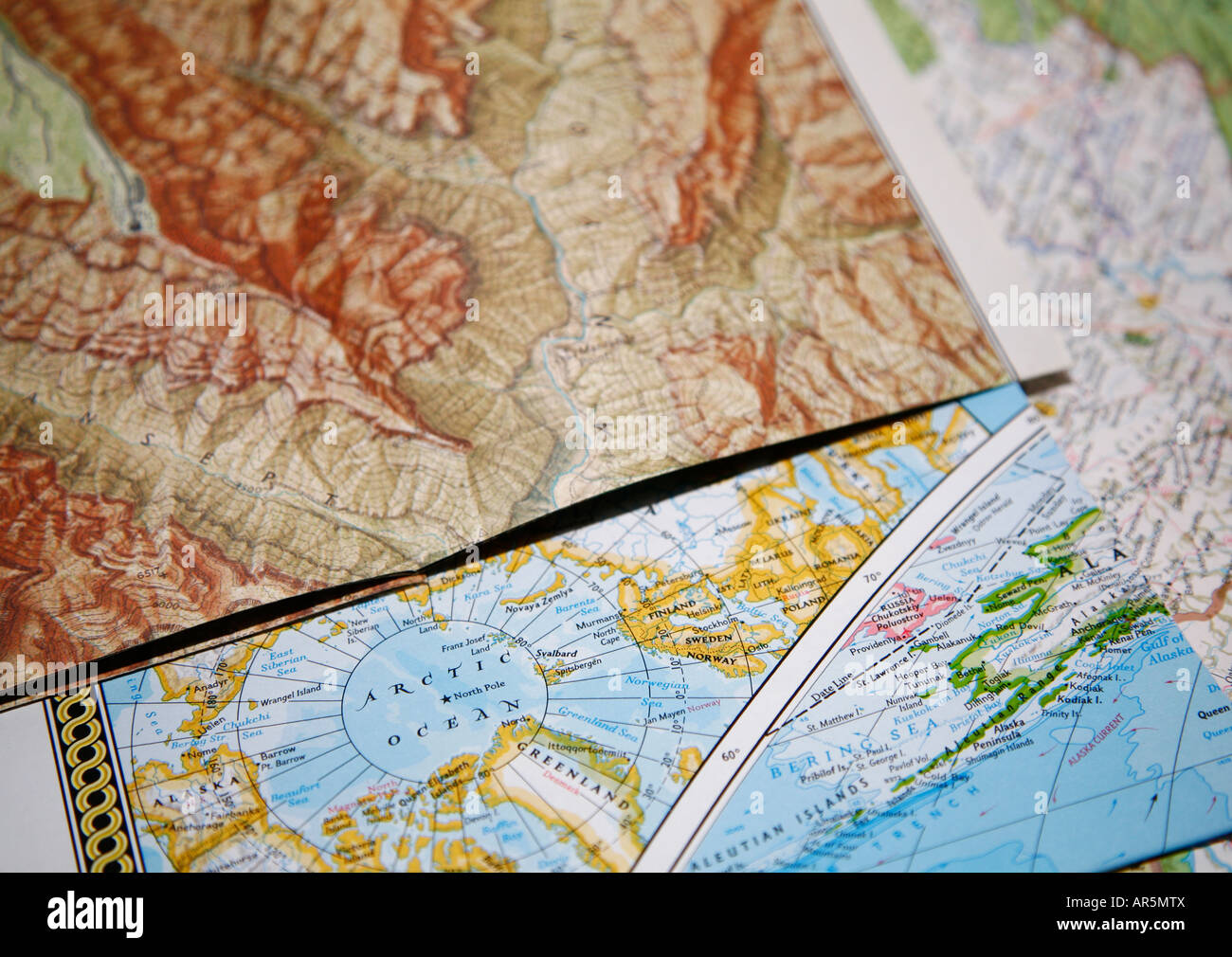 close up of road maps lying on top of each other map of mountain area and map of arctic area with north pole shallow dof