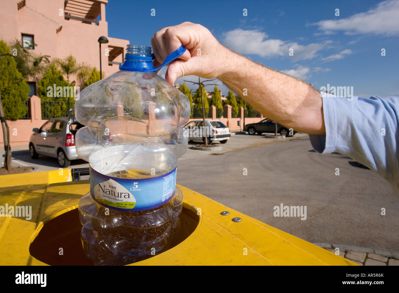 Close up of senior mans arm throwing plastic bottle in to recycle bin - Stock Image