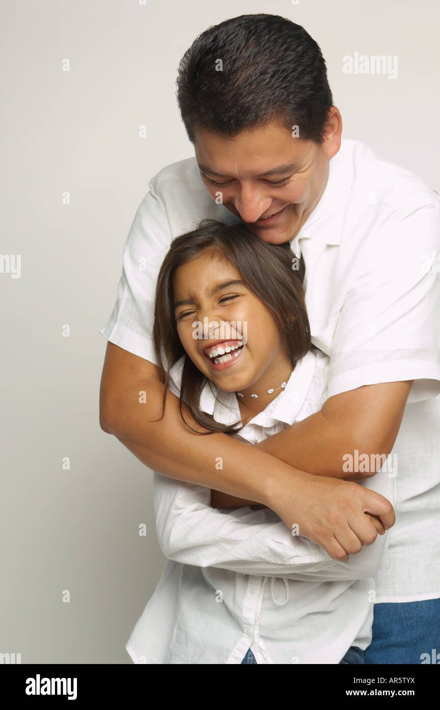 Hispanic father and daughter hugging Stock Photo