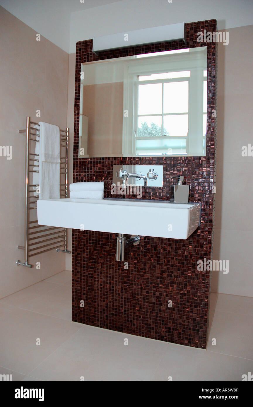 bddf9975443de Large mirror above rectangular white ceramic basin on brown mosaic ...