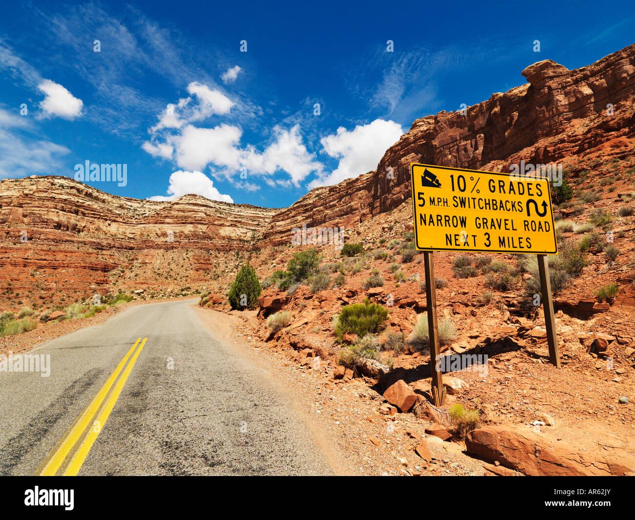 Road sign warning steep grade through rocky Utah landscape - Stock Image
