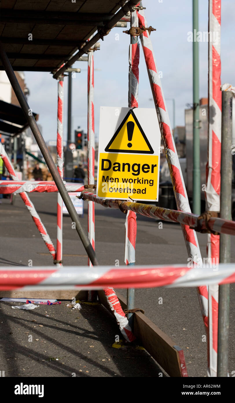Warning sign under scaffold poles on a pavement. Shot in the UK - Stock Image