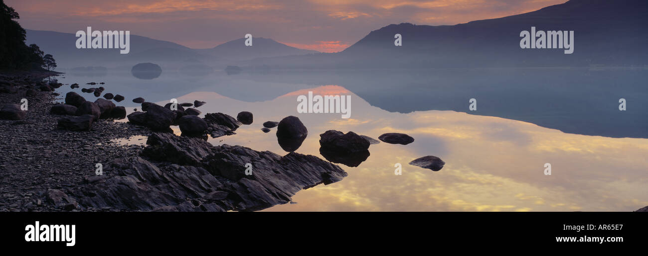 Dawn is breaking on the far misty shore of Derwentwater Cumbria - Stock Image