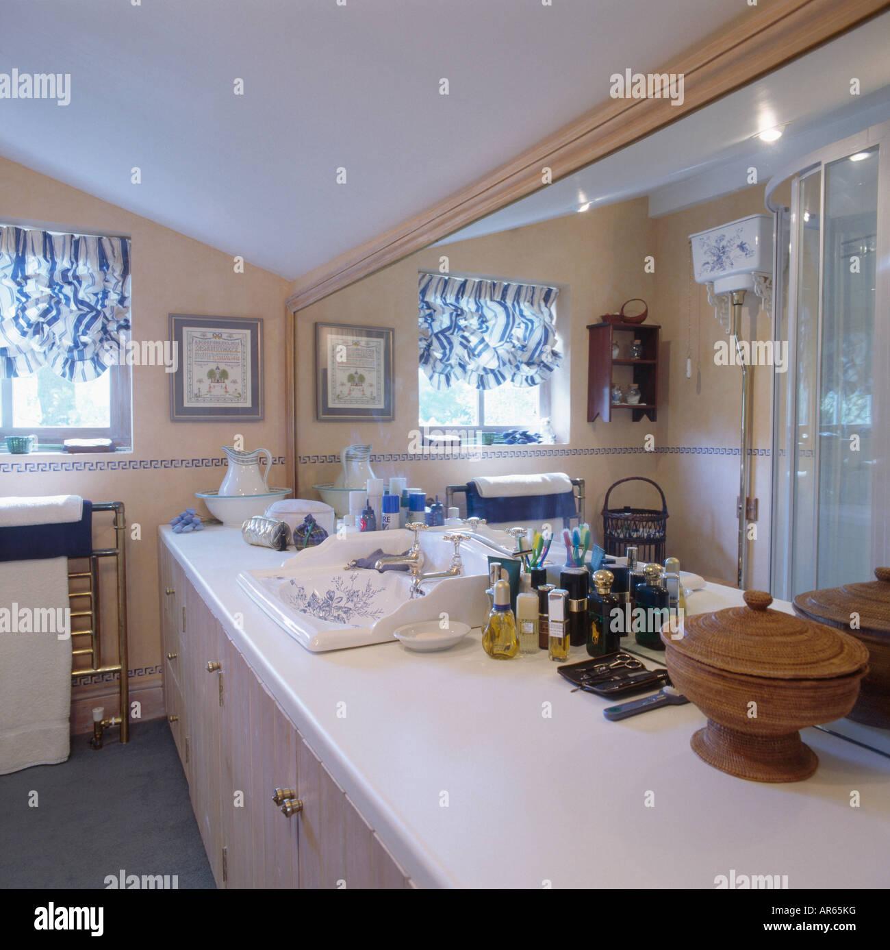Perfume bottles on vanity unit below long mirror in town bathroom - Stock Image