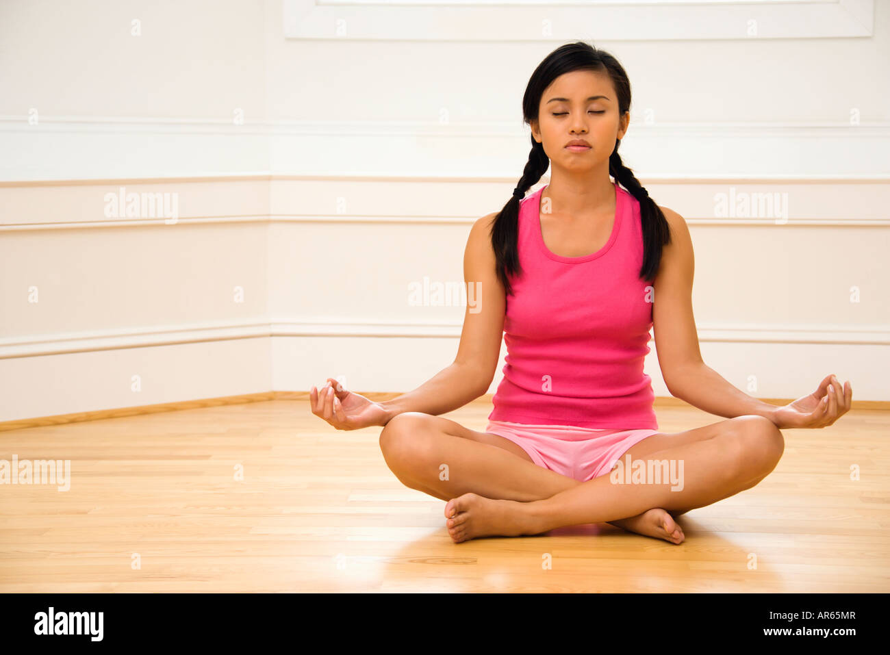 Young woman sitting on floor meditating in yoga lotus pose with legs crossed and eyes closed - Stock Image