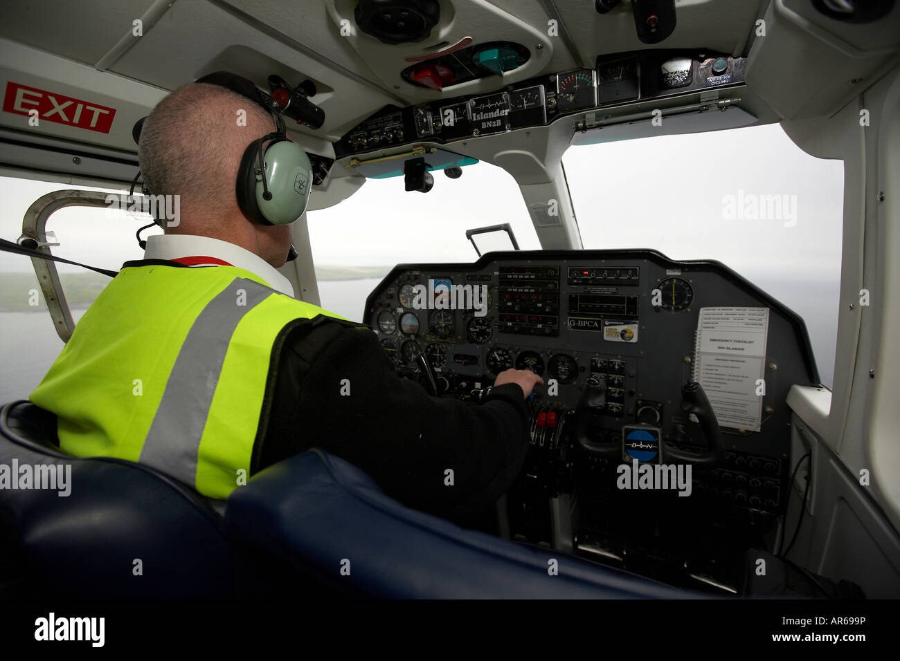 Pilot flying a Britten Norman Islander aircraft to North Ronaldsay Orkney Scotland UK - Stock Image