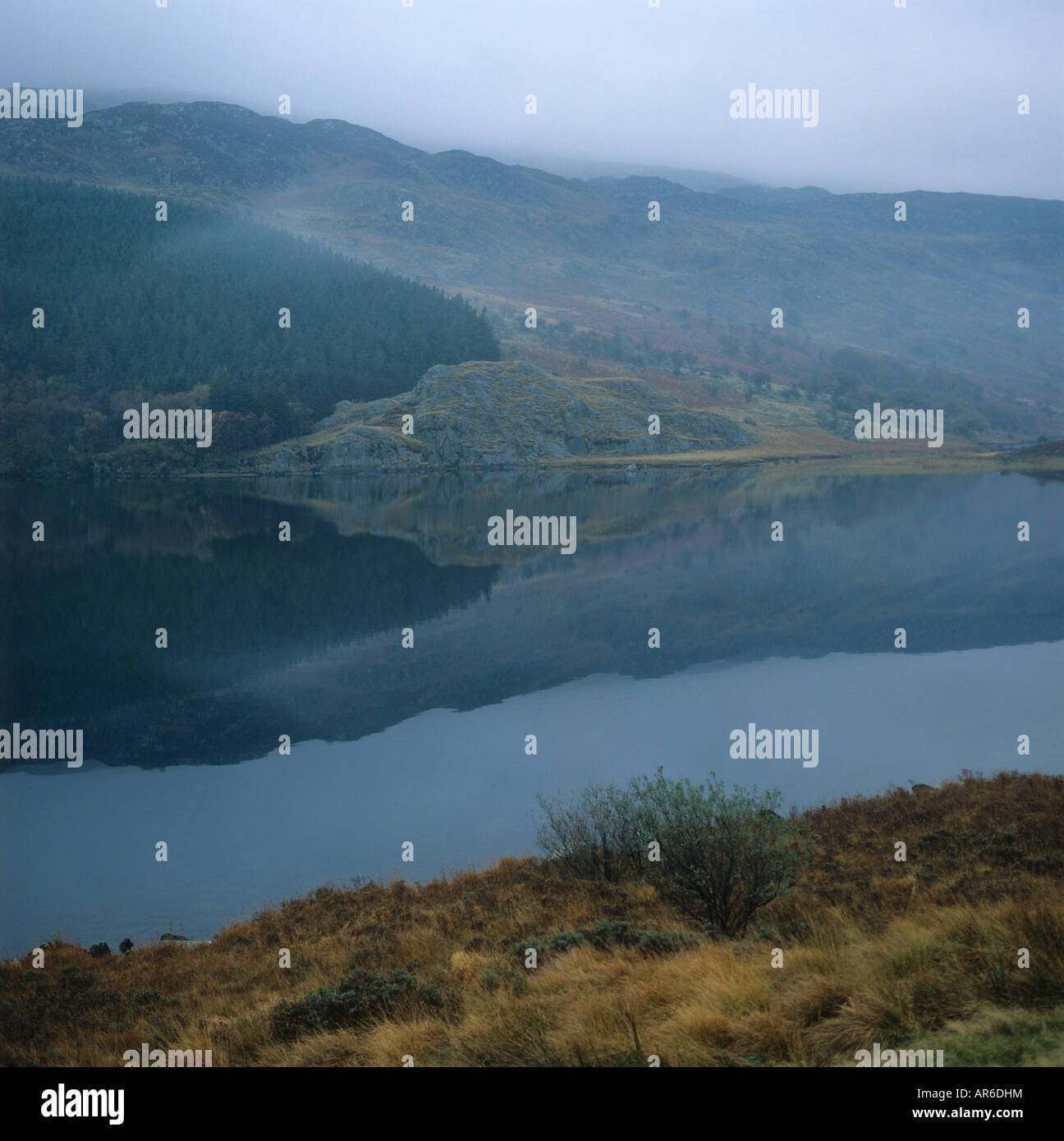 Misty dull day with reflections in a still mountain lake in Snowdonia Wales - Stock Image