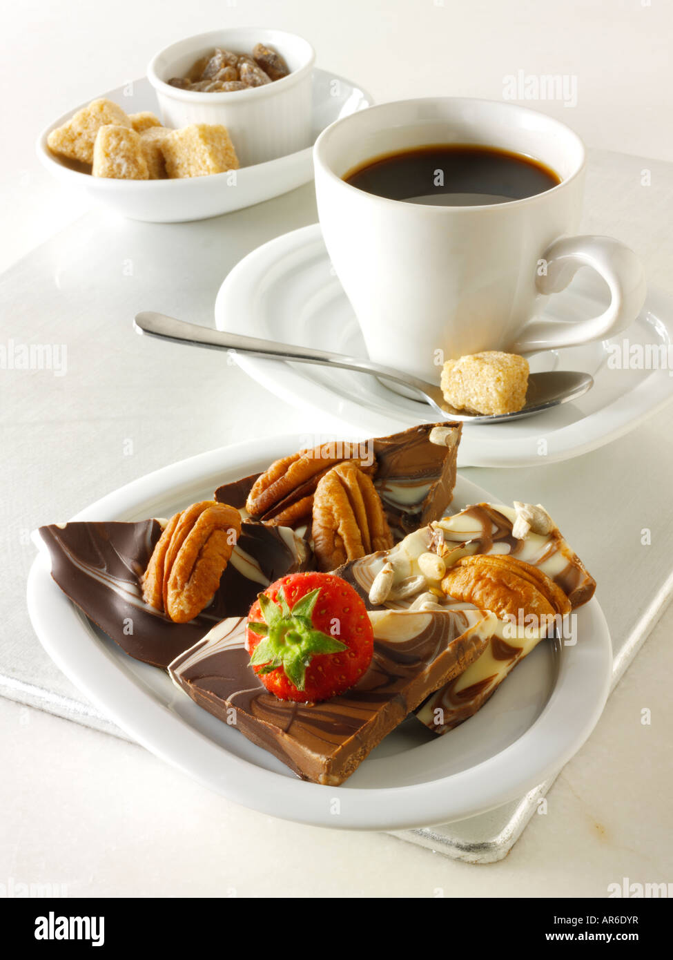 Chocolate swirls squares with fresh strawberries and pecan nuts on a tray with black coffee. - Stock Image
