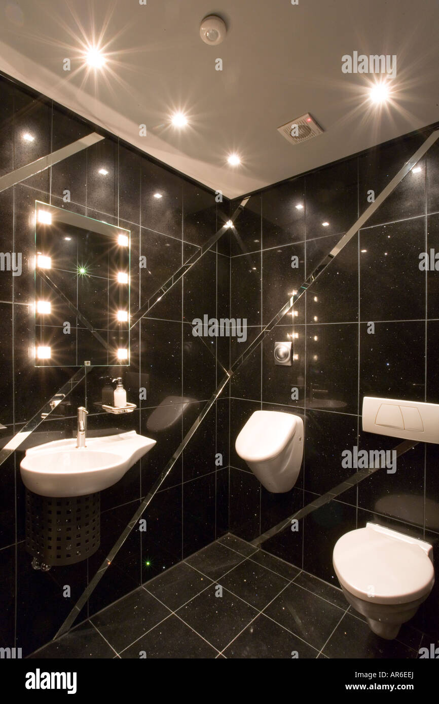 Modern black tiled toilet with angled mirrors and sunken halogen ...