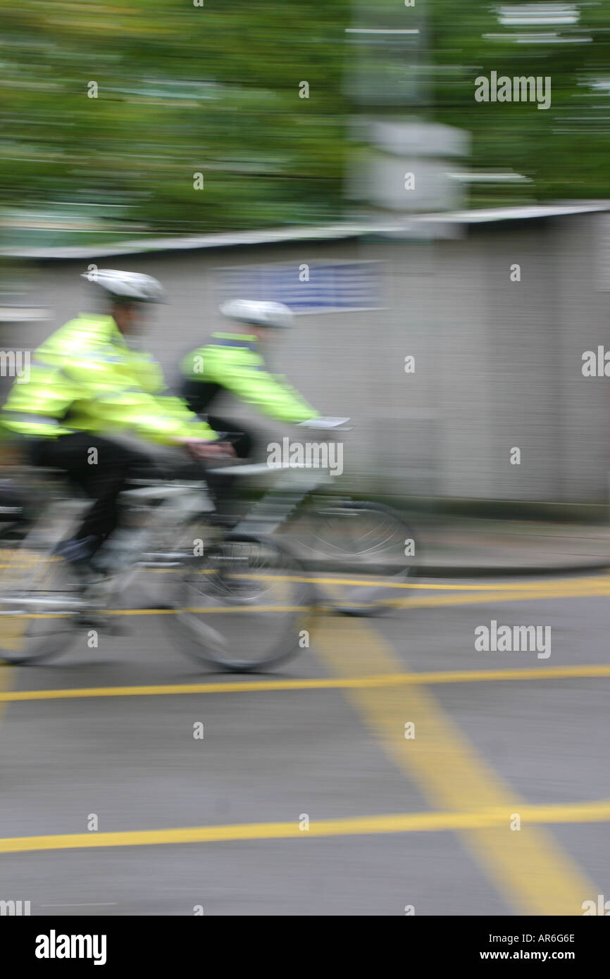 Two police men on mountain bikes patrolling an anti-social behaviour exclusion zone, Finsbury Park, London UK, - Stock Image