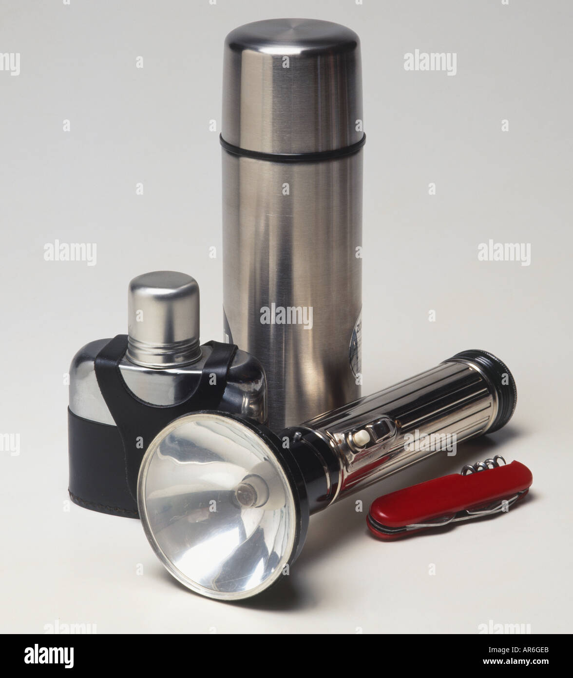 Selection of basic survival equipment; metal drinking flask, torch, hip flask, and penknife. - Stock Image