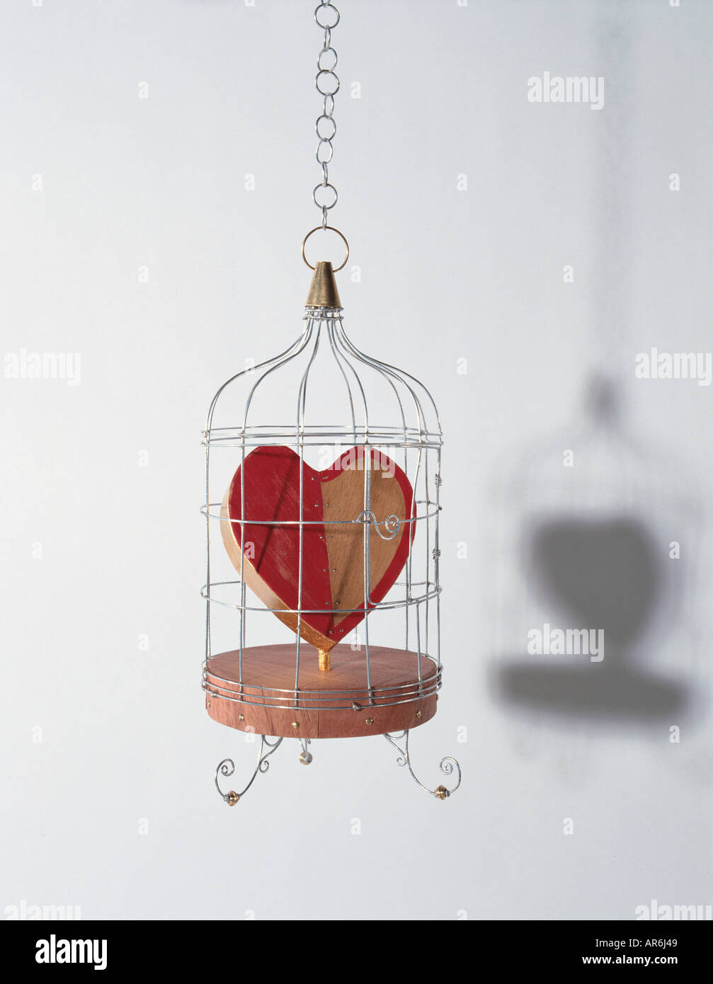 Wooden love heart hanging trapped in a metal birdcage, heart painted half red, solid wooden base - Stock Image