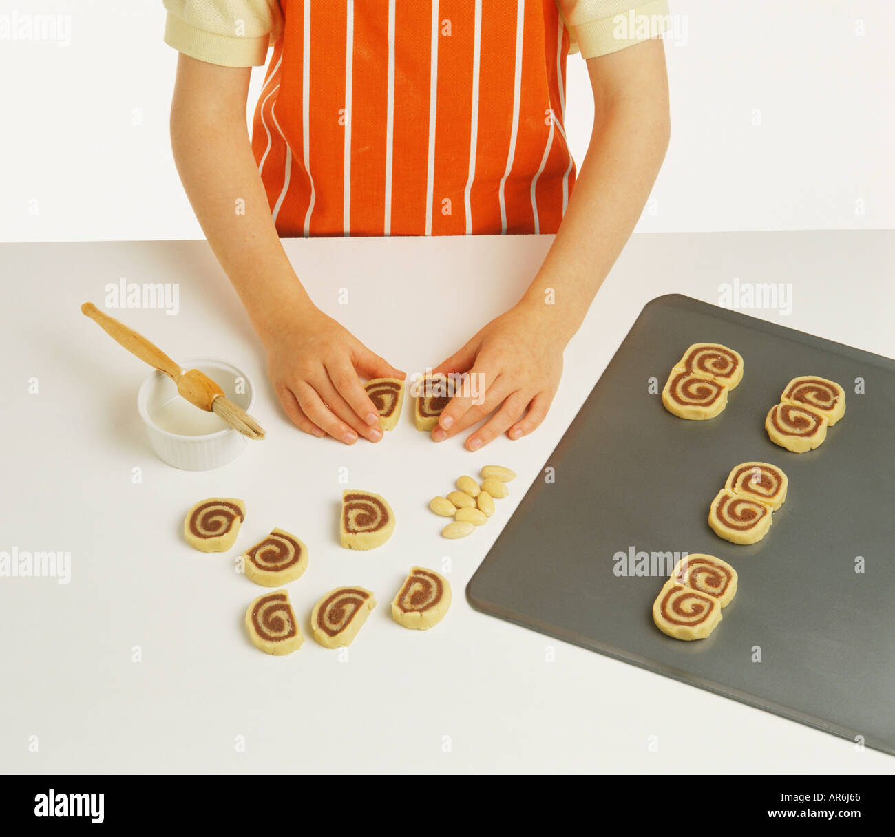 hand model wearing orange and white striped apron cook joining two biscuits to make owls eyes