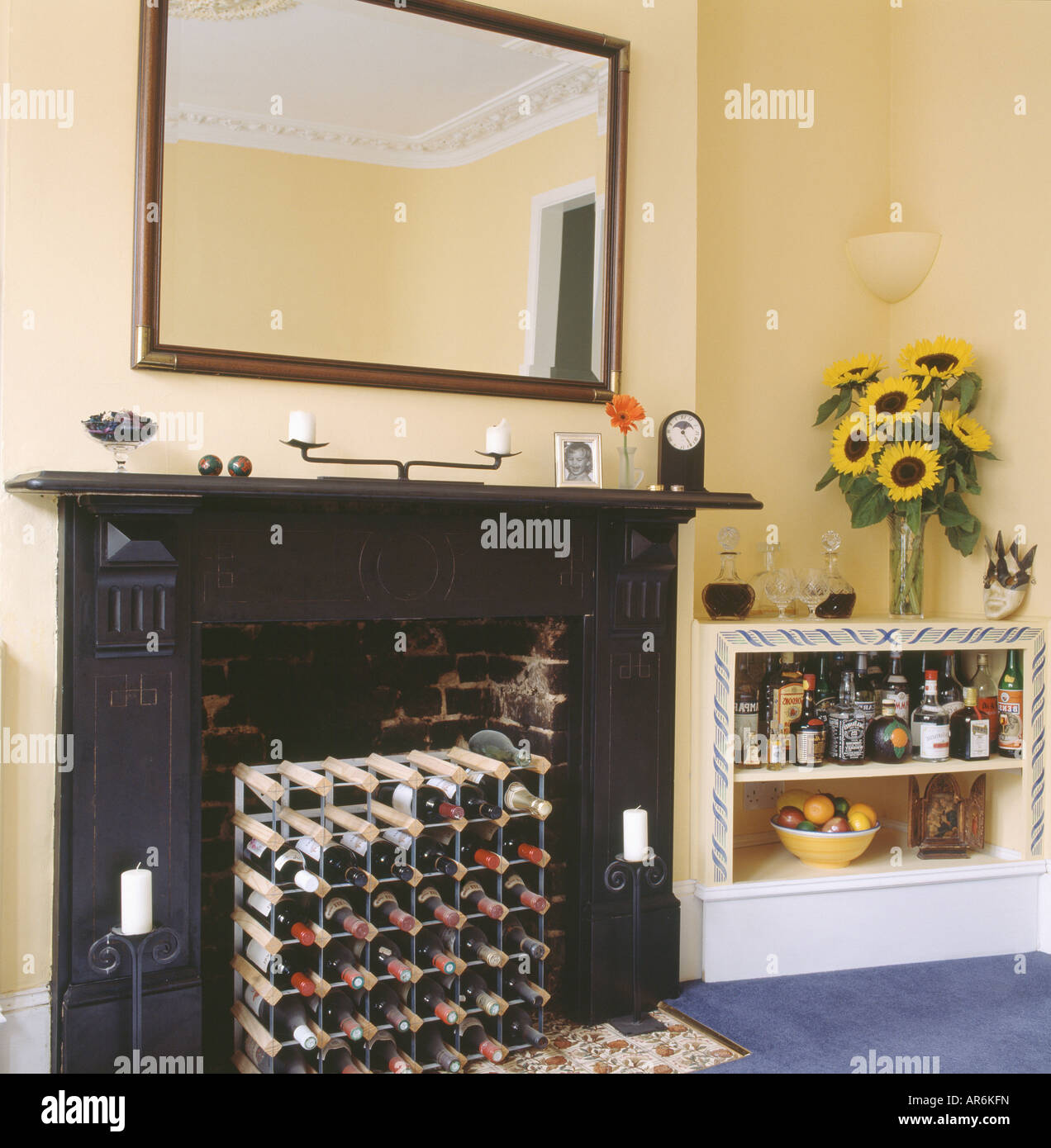 Etonnant Wine Storage In Fireplace Below Large Mirror In Pastel Yellow Dining Room  With Sunflowers And Liqueur Bottles On Shelving