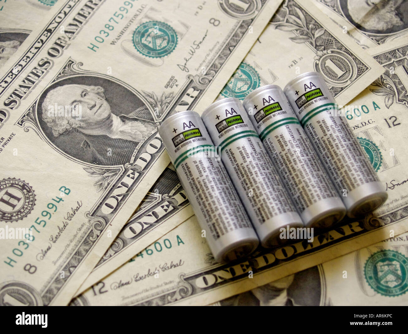 Four silver colored NiMH AA battery cells against a background of dollar bills. Stock Photo