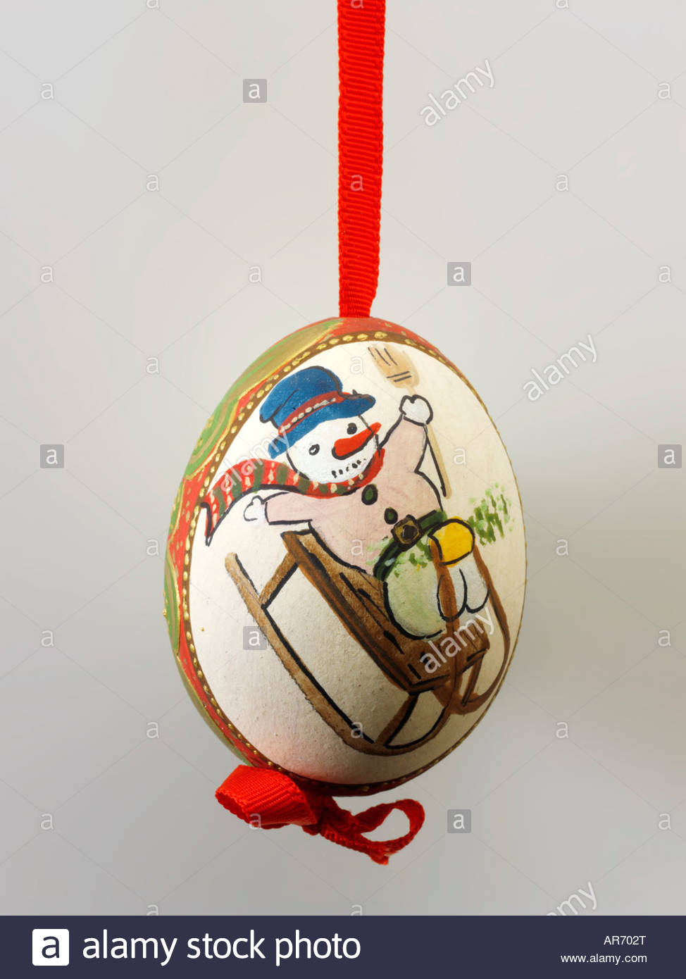 traditional  festive decorted egg Christmas tree bauble with a  painted snow man and Sledge - Stock Image