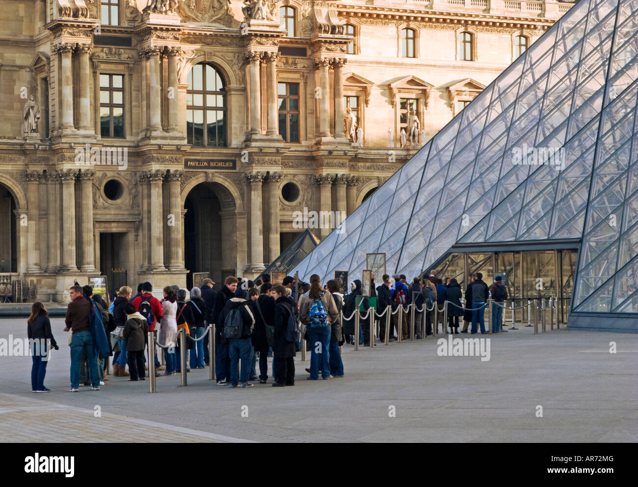 Louvre Museum, Paris, France, Europe - Visitors queue up early in the morning at the Louvre Pyramid entrance - Stock Image