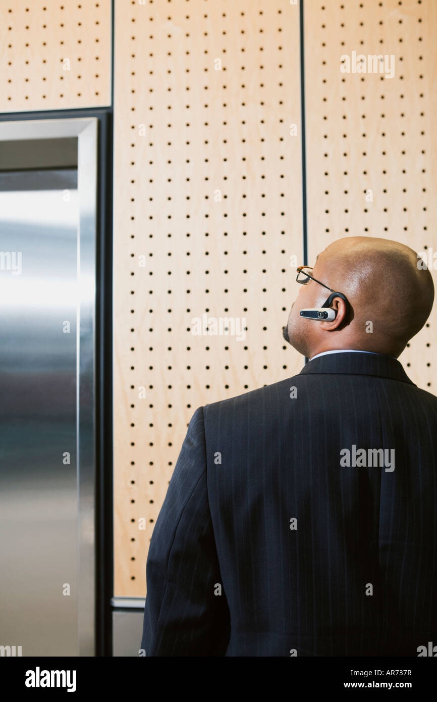 African businessman looking at elevator Stock Photo