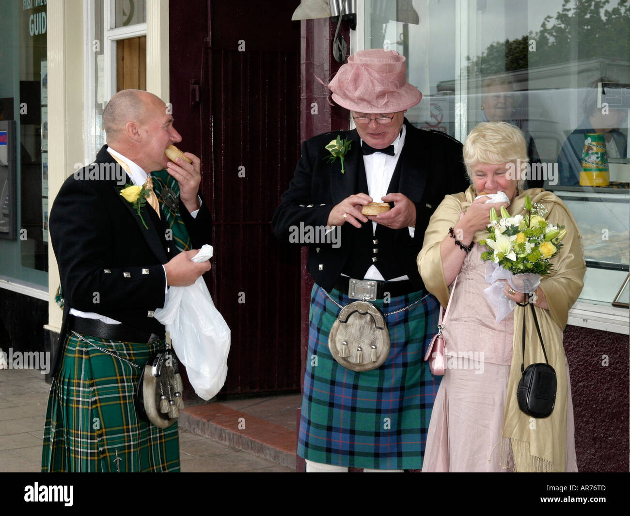 Wedding guests (man wearing ladies hat) eating out in Gretna Green Scotland Stock Photo