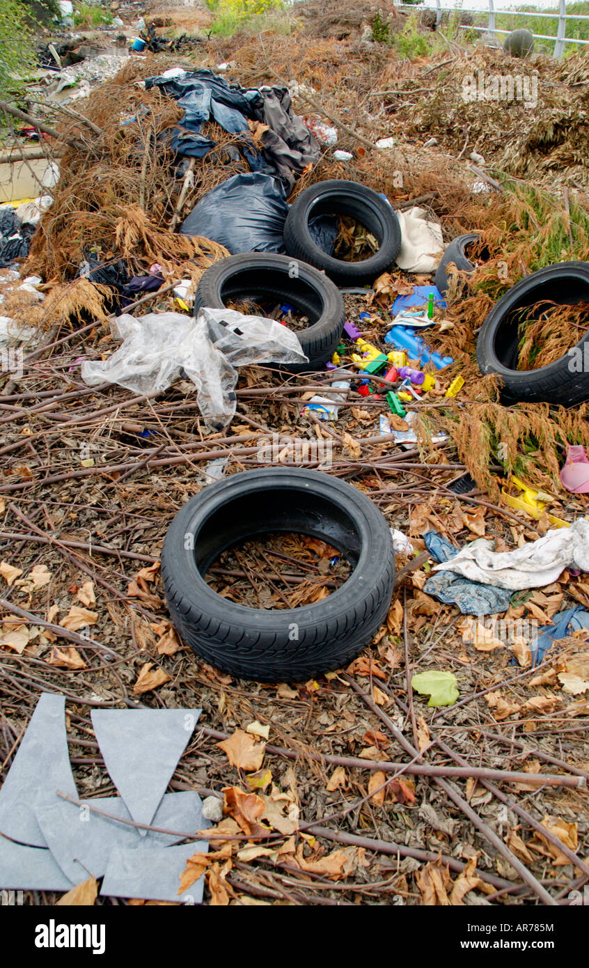 Car tyres and garden waste dumped on waste ground near the city centre Newport South Wales UK EU - Stock Image