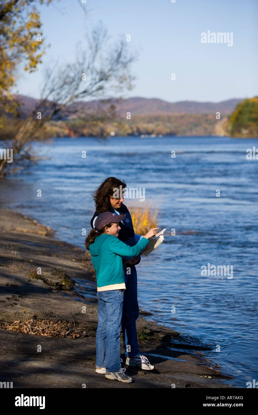 A mom and her daughter birdwatching on the banks of the Connecticut River in Holyoke, Massachusetts. - Stock Image