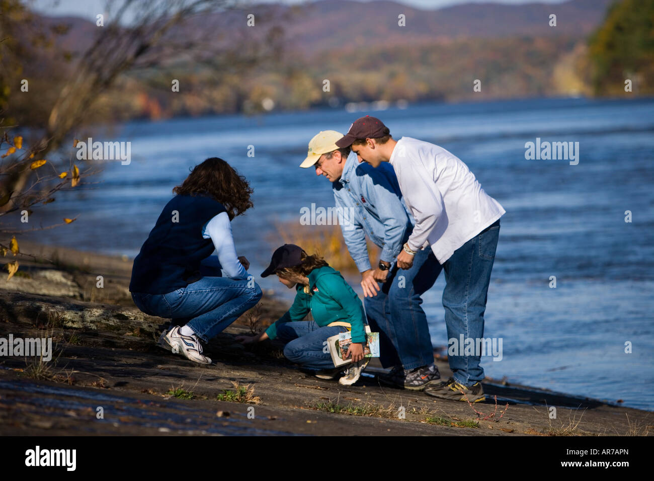 A family studies nature on the banks of the Connecticut River in Holyoke, Massachusetts. Stock Photo