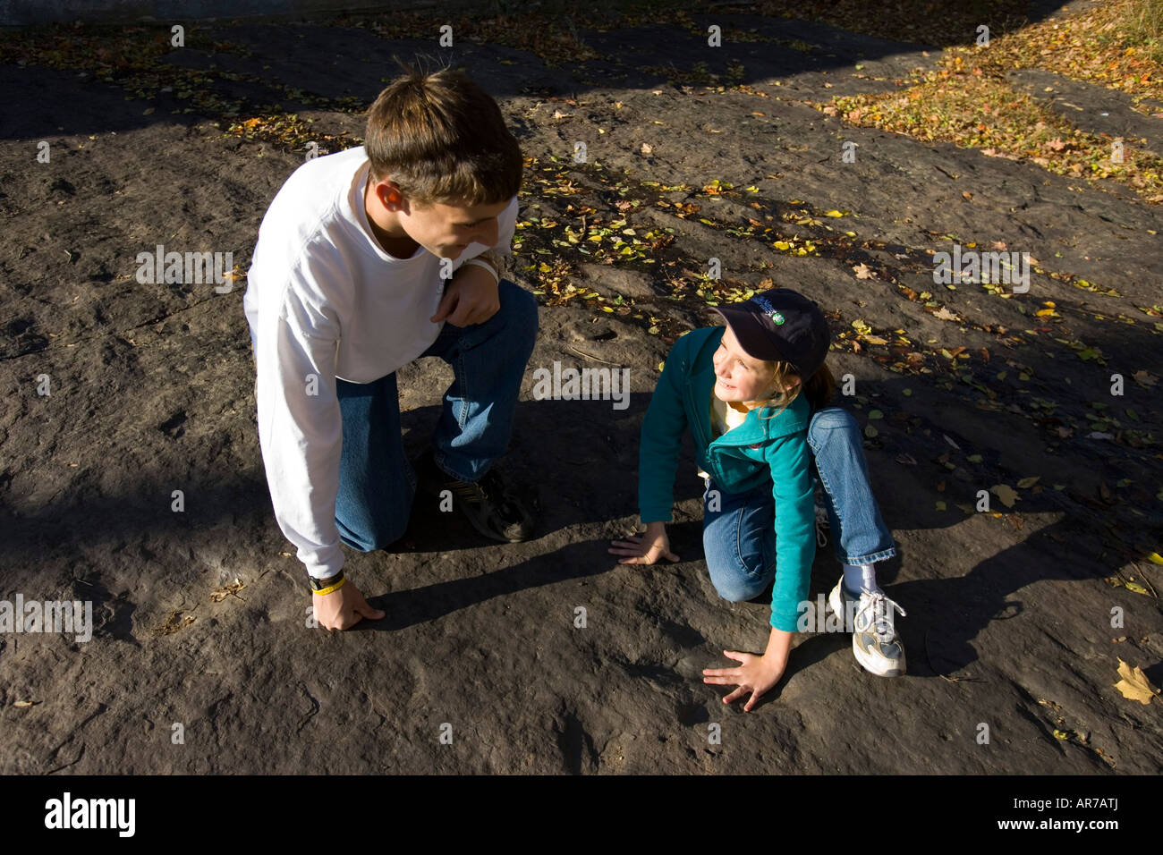 A brother and sister look at a dinsaur footprint near the Connecticut River in Holyoke, Massachusetts. - Stock Image