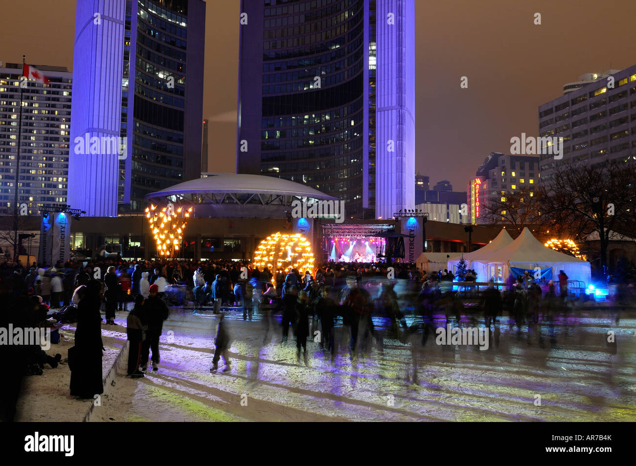 Skaters on ice rink at Toronto City Hall during Wintercity Nights of Fire and Weakerthans rock musicians stage show - Stock Image