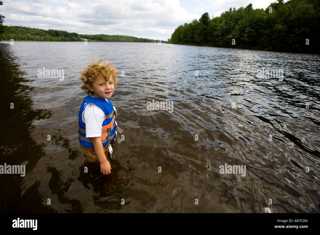 A young boy (age 4) plays in the Androscoggin River in Turner, Maine. - Stock Image