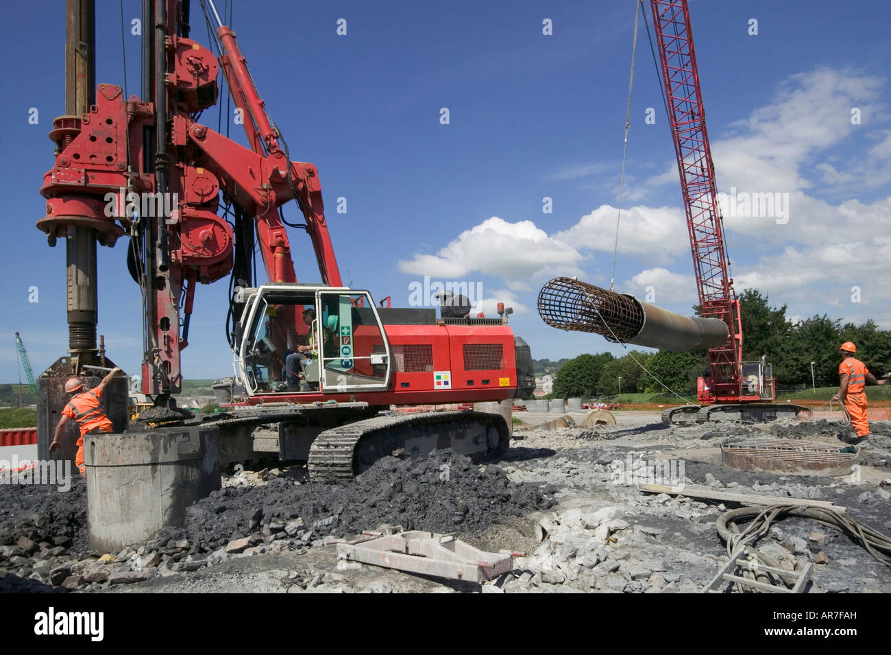 Huge piling rig discharging spoil.  Behind, a crane lifts a reinforced steel cage to insert into pile before concrete - Stock Image